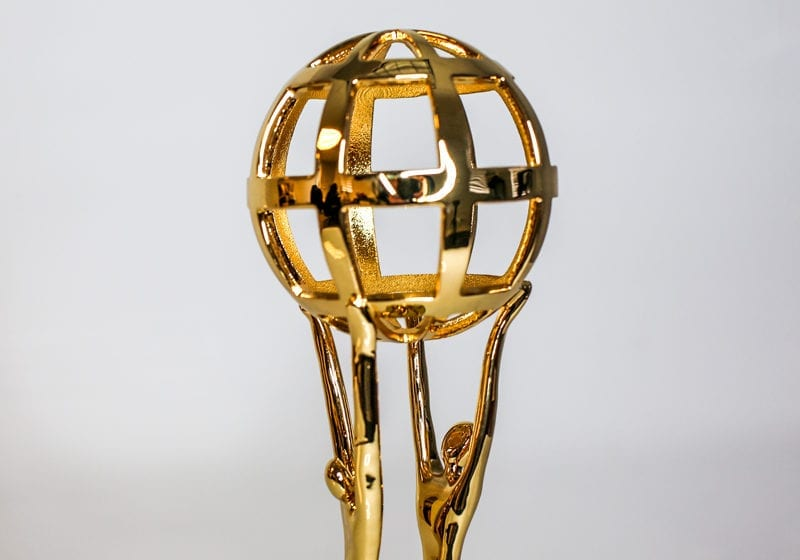 Polished Golden Award Statue Of Two Figures Holding Up A Globe